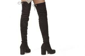 Woman legs in black suede boots on white background